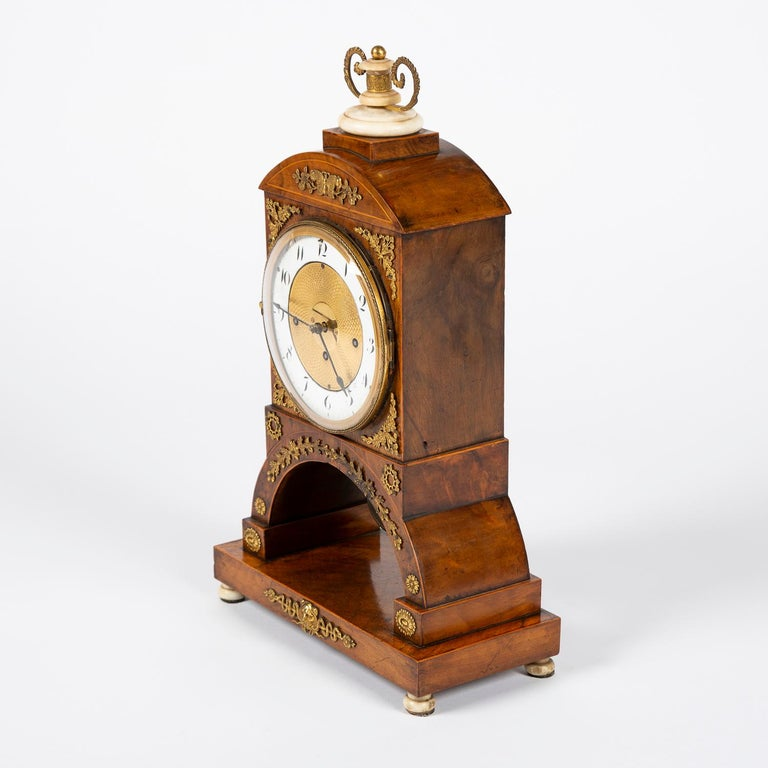 A three train walnut and marble Biedermeier mantle clock with ormolu mounts, circa 1820.  Walnut case with boxwood stringing, gilded bonze floral mounts, engine turned dial and a white enamel chapter ring with Arabic numerals.  The triple train
