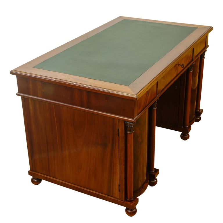 Recently fully refinished with writing surface resurfaced in green leather. This desk features two highly adorned barrel fronted storage cabinet topped by a three drawer writing surface. Original keys and hardware are fully functional.