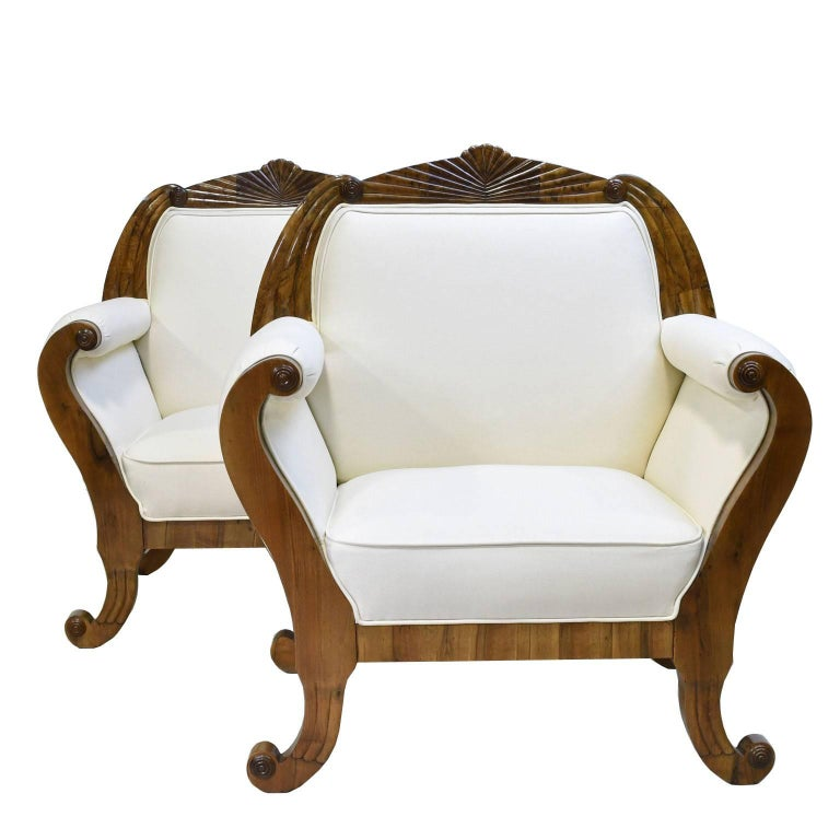 A very beautiful South German Biedermeier suite in Fine walnut consisting of a sofa and a pair of armchairs/ bergères, each with shaped, fan-carved crest rail above scrolled armrests terminating in out-scrolled feet, Germany, circa 1830. Note: Our