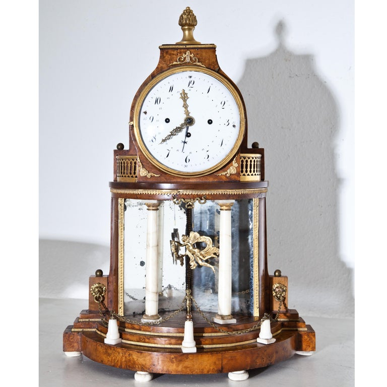 Biedermeier portal clock in an architecturally structured walnut case with alabaster columns, bronze fittings and mirrored rear wall. The clockwork with date and sound spiral. Pendulum in the shape of a winged putto.