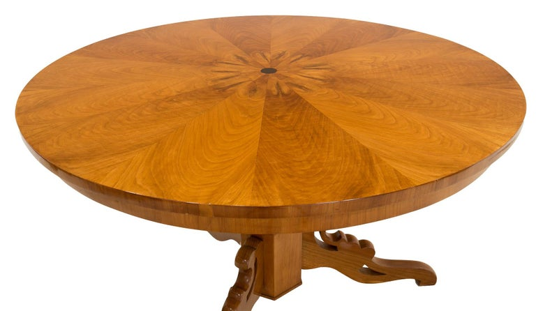 This Biedermeier round table was made in Germany in 19th century. It is supported on a beautifully sculpted leg made of cherrywood, the tabletop is also veneered with cherrywood. The piece has been refinished with varnish which besides great visual