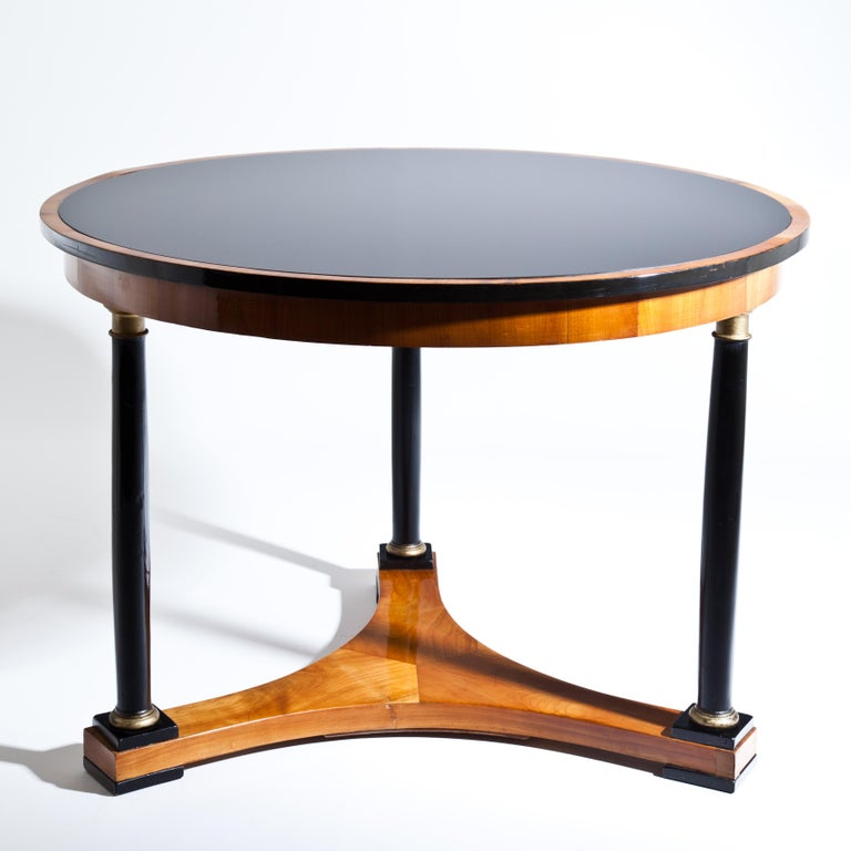 Biedermeier salon table in cherry, with round tabletop on three ebonized and partly gold-patinated column legs above a concave stand. The blackened tabletop with likewise ebonized edge has a recent glass top.