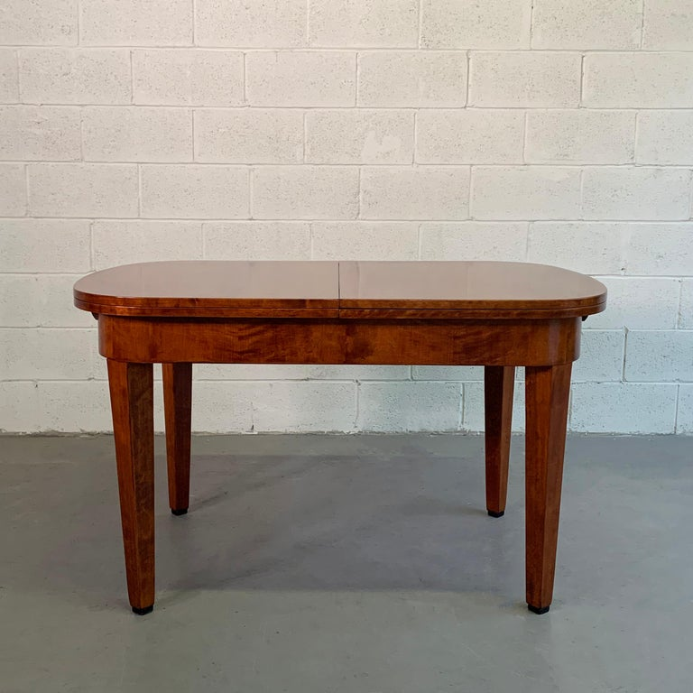 Antique, Biedermeier period, two-tone, satinwood, dining table by Ruscheweyh Tisch , Germany, features 2 leaves that tuck underneath that expand the table to 87 inches wide. The legroom height with lip is 23.25 inches.