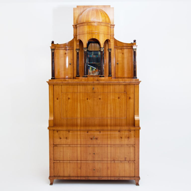 A secretaire with writing flap and an architectural top with partially gilded columns and half-dome rising above a three-drawered chest of drawers. Two concave side doors with slightly rising cornice lead to the high semi-dome with stepped top. The