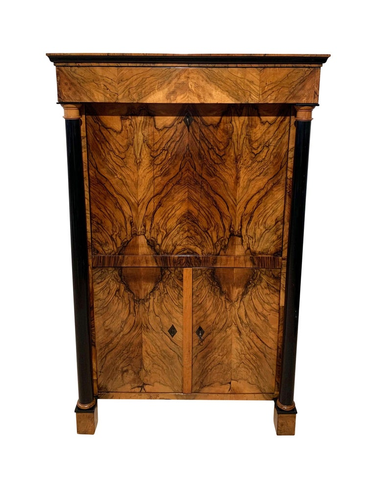Very elegant, neoclassical early Biedermeier Secretaire from Southwest Germany, circa 1820.  Outstanding book-matched walnut veneer on softwood, French polished with shellac. Ebony hash shaped key escutcheons. Ebonized full columns, writing plate