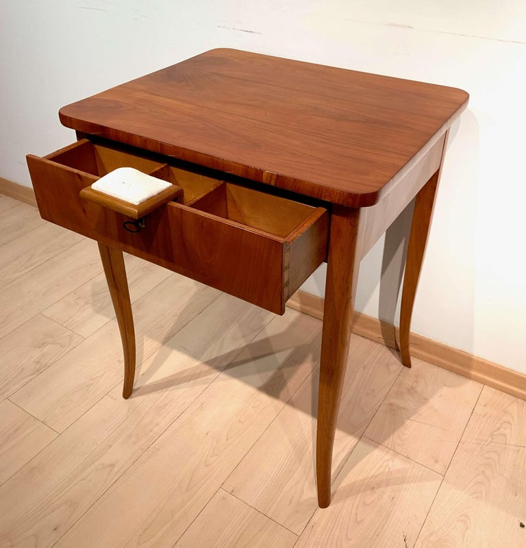 Classic Biedermeier sewing table  Curved square-pointed legs. 1 drawer with interior. Cherry veneered (plate and apron) and solid wood (legs)  Ivory or bone around the keyhole.