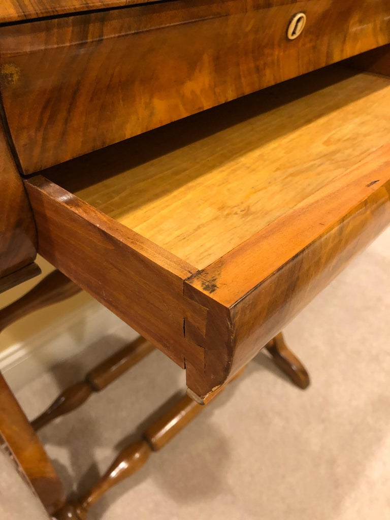 Original Biedermeier sewing table, South German 1820, walnut veneer. Beautiful table with exquisite veneer grain on the top. Two drawers, the upper one with small compartments and a pincushion. The table is in good condition and has a nice patina.