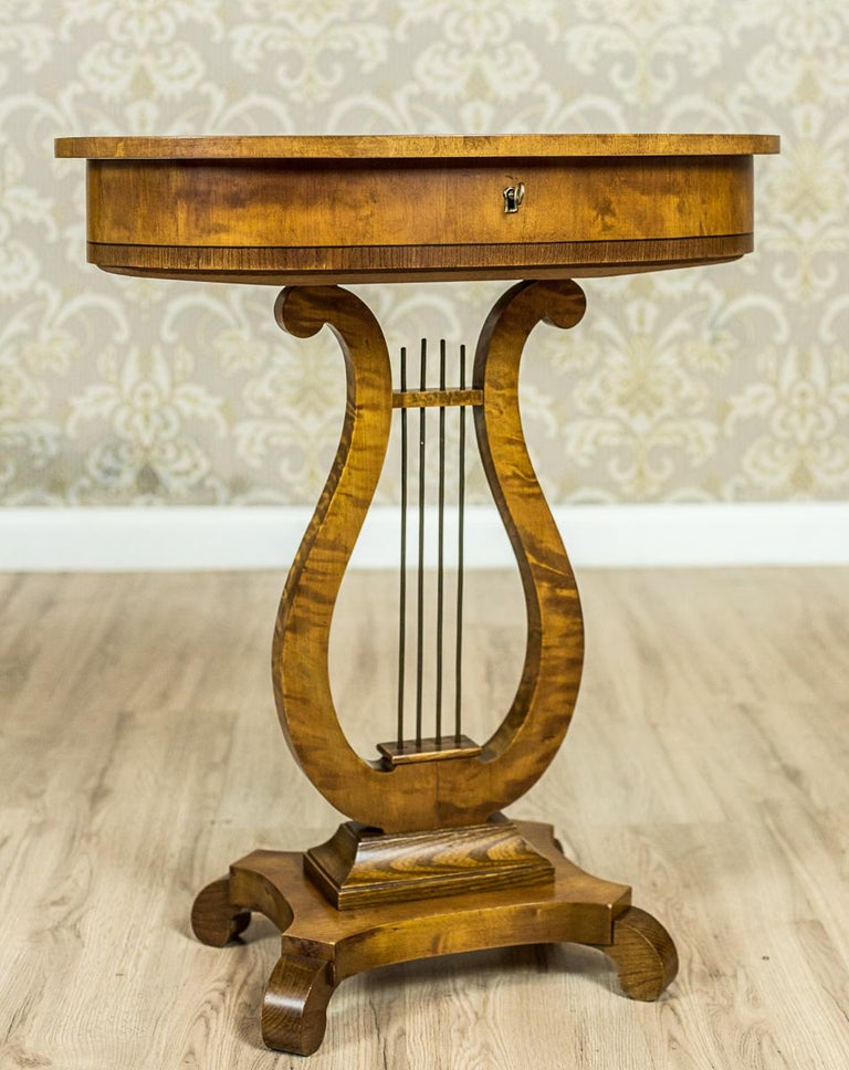 We present you a beautiful sewing table. This piece of furniture, circa the 1950s, is in birchen veneer, and is stylized as the Biedermeier furniture. The oval top, along with the apron, are supported on a leg in the shape of a lyre, which is