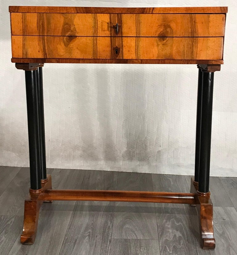 Biedermeier side- or sewing table, South German 1815, walnut veneer.  This classic unique Biedermeier table has two ebonized columns on each side, which stand on a walnut base connected with a stretcher. The plain rectangular top has two drawers.