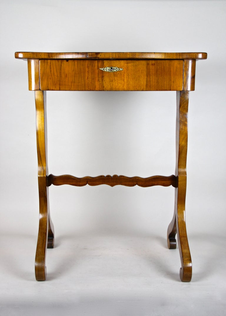 Absolute lovely Biedermeier side table coming from the second Austrian Biedermeier period circa 1850. After 169 years this small table is still an eye-catcher and comes with a big center drawer, divided into four compartments. The beautiful nut wood