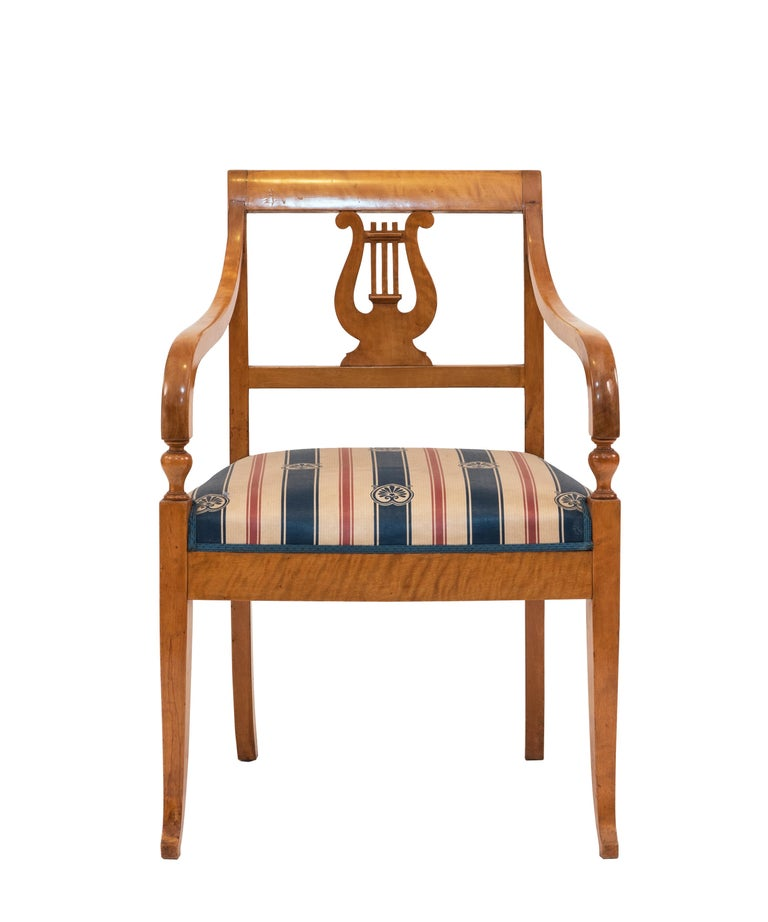 Swedish Biedermeier style (19th-20th Century) birch armchair with lyre carved back and blue stripe upholstery.