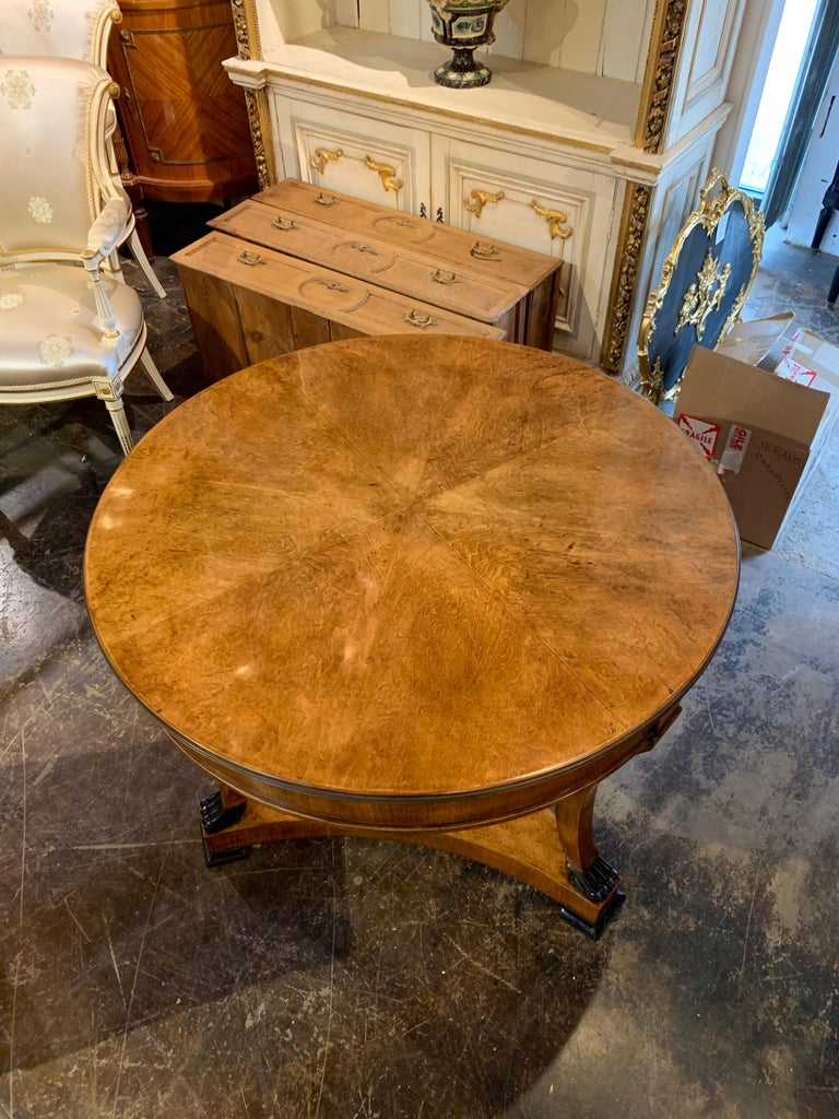 Very handsome Biedermeier style center table with ebonized claw feet. Beautiful finish on this piece and there is also brass along the top edge of the table. An absolute gorgeous table that creates a lovely polished look!