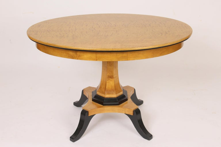 Biedermeier style oval occasional / center table, circa mid-20th century. With an oval feather birch top and ebonized feet.