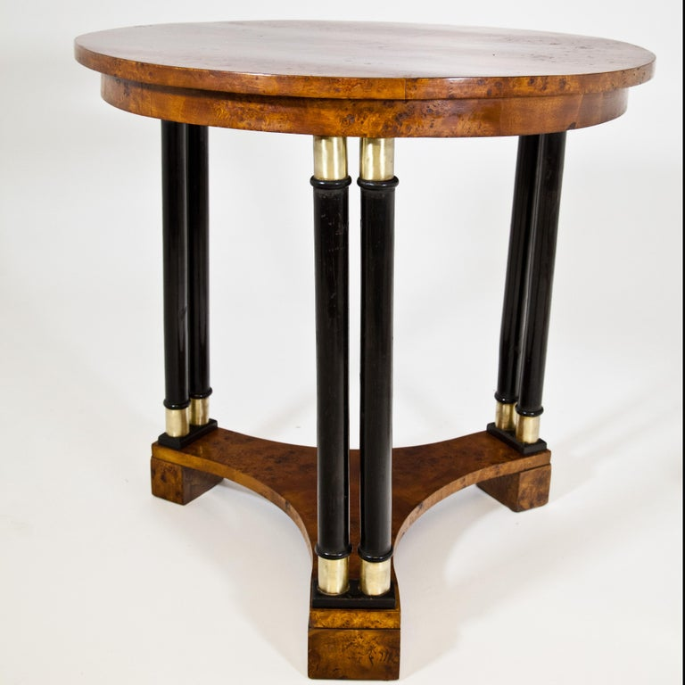 Round table standing on three double columns with poplar grain veneer and concave strutting between the legs. The bases and capitals of the ebonized columns are made of brass. Expertly restored condition.
