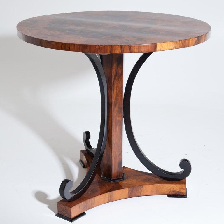 Biedermeier table with round tabletop on three ebonized C-shaped legs around hexagonal column stand over triangular foot. Walnut burl veneered. Hand polished condition.