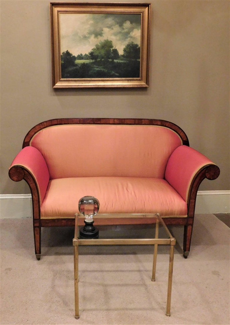 This neoclassic loveseat was probably made in what is now Germany or in Austria. The small sofa has a frame of mahogany inlaid with satinwood. The roll arms end in a sunburst inlay. The brass castors appear to be original. The settee was upholstered