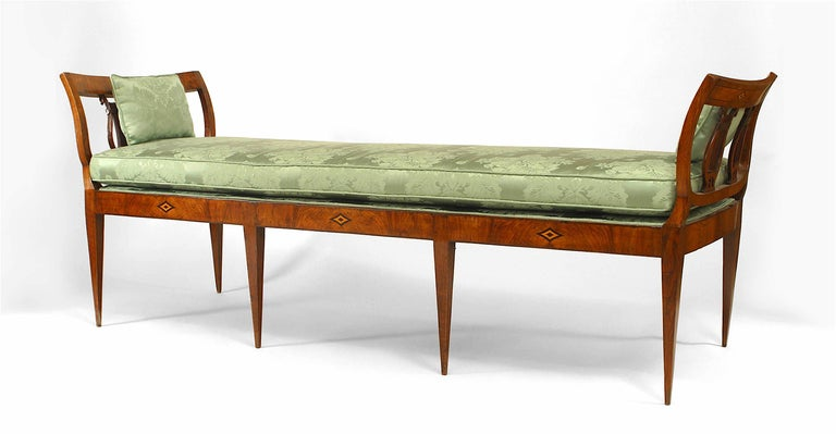 German Biedermeier walnut bench / daybed on tapered legs with open double lyre side arms and marquetry diamond design inlay with green upholstered seat cushion.
