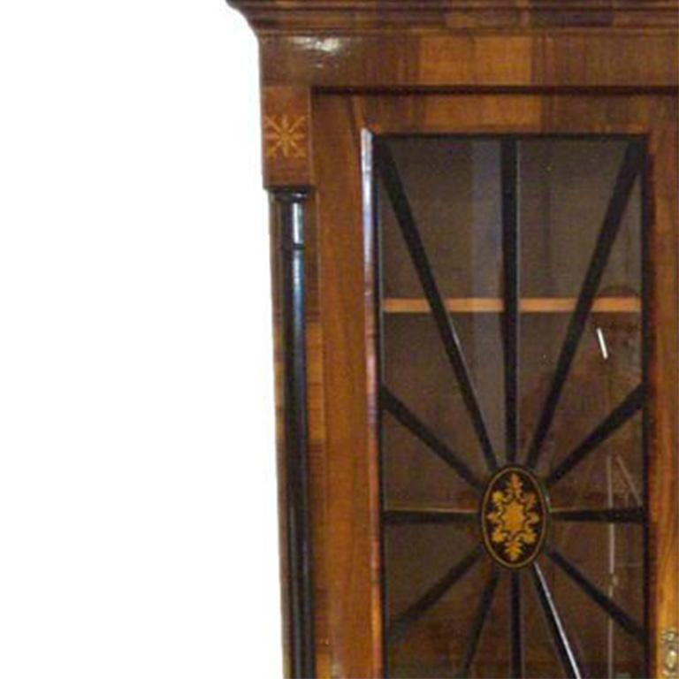 Biedermeier Vitrine/Bookcase – walnut, rootwood and ebonized wood and columns with brass hardware.  Glazed doors with ebonized columns in spindle pattern and interior shelves.