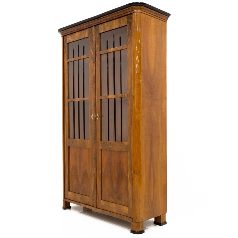 This Biedermeier style vitrine comes from Germany from circa 1830-1850. It is made of coniferous wood, veneered with beautiful walnut veneer with a very decorative design. The piece is after complete and professional renovation process. The surface