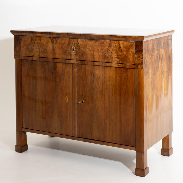 Half cupboard with wide top drawer and two doors, standing on plinthed square feet. Very beautiful walnut veneer. The sideboard has been expertly hand polished.