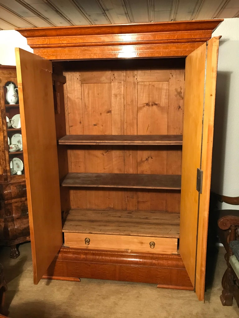 Biedermeier Wardrobe, Baltic States 1810-1820, Bird's-eye maple veneer, filament inserts on the doors and the pilaster strips. Inside one drawer and a coat rack. Two shelves have been added later. The wardrobe is in very good condition. It will ship