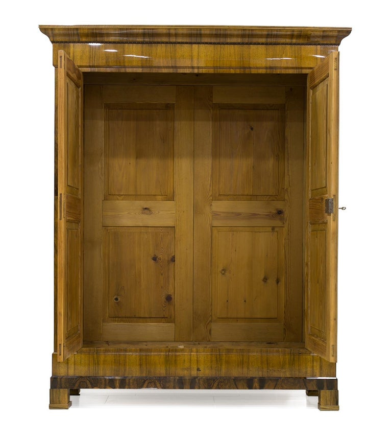 This Biedermeier wardrobe was made circa 1830 and is preserved in very good original condition. The piece was subjected to a very subtle, professional and careful renovation. The wardrobe is made of pine wood, veneered with walnut in a unique
