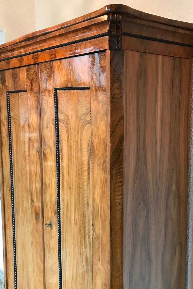 Biedermeier wardrobe, South German 1820, walnut veneer with ebonized and hand carved details. Two doors with shelf's on the left side and two rows of coat racks on the right side. In very good condition. The wardrobe will be shipped from Germany.