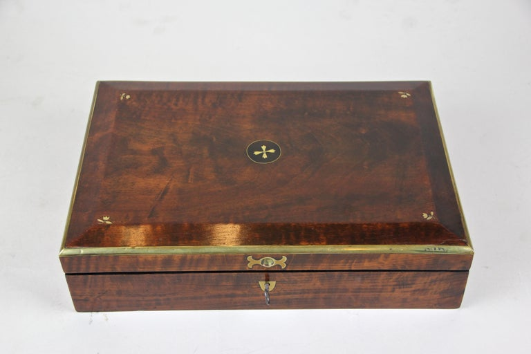 Precious Biedermeier wooden box out of Vienna/ Austria, circa 1830. This enchanting nut wood veneered box comes with wonderful brass framed edges on the lid, where you can also find beautiful small mother of pearl inlayed flowers. With an age over
