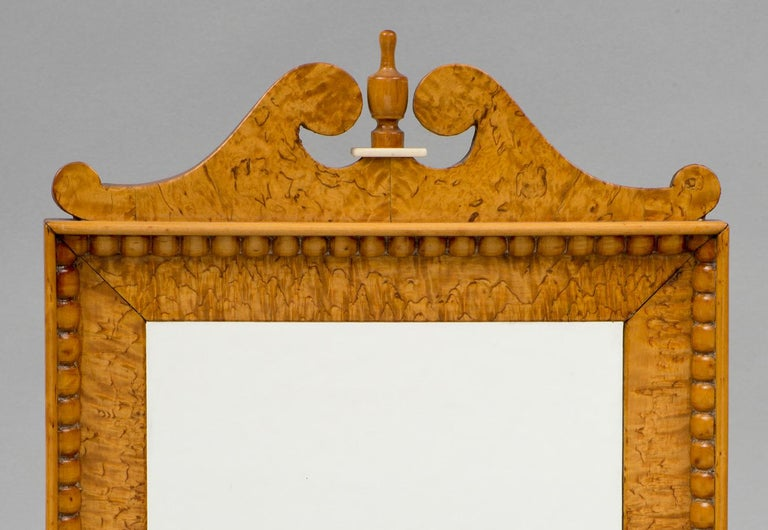 Biedermeir mirror in a burled maple frame, topped by a swan neck pediment with urn shaped finial on a bone base. The inside border has hand carved beading all around.
