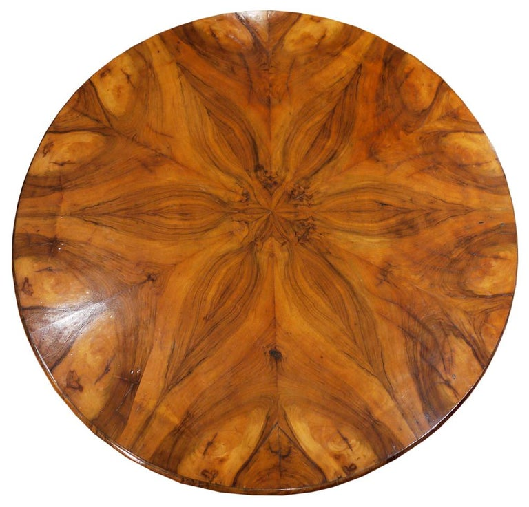Round Biedermeier table in walnut and walnut root. The top is veneered in walnut, divided into twelve segments to create suggestive veining games. The central ball-shaped stem is flanked by three shaped and carved uprights. Small triangular base.