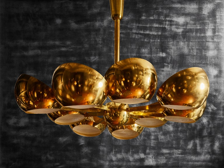 Big brass chandelier with nine arms of light. Each source of light is hidden with a glass textured lens.