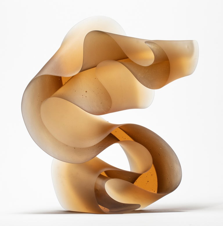 Big line in amber is a unique cast glass sculpture in amber glass, created by the Danish artist Karin Mørch. Dramatic sweeping curves meander and follow the beautiful lines of this heavy and solid cast piece. Mørch intimately understands her glass