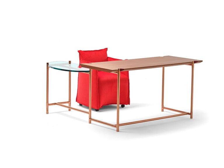 An original desk with a wooden top and a glass extension that can rotate around a central pivoting point, like the hand of a clock. This allows the table to expand and contract its usable surface and to adapt to different uses: a dedicated support