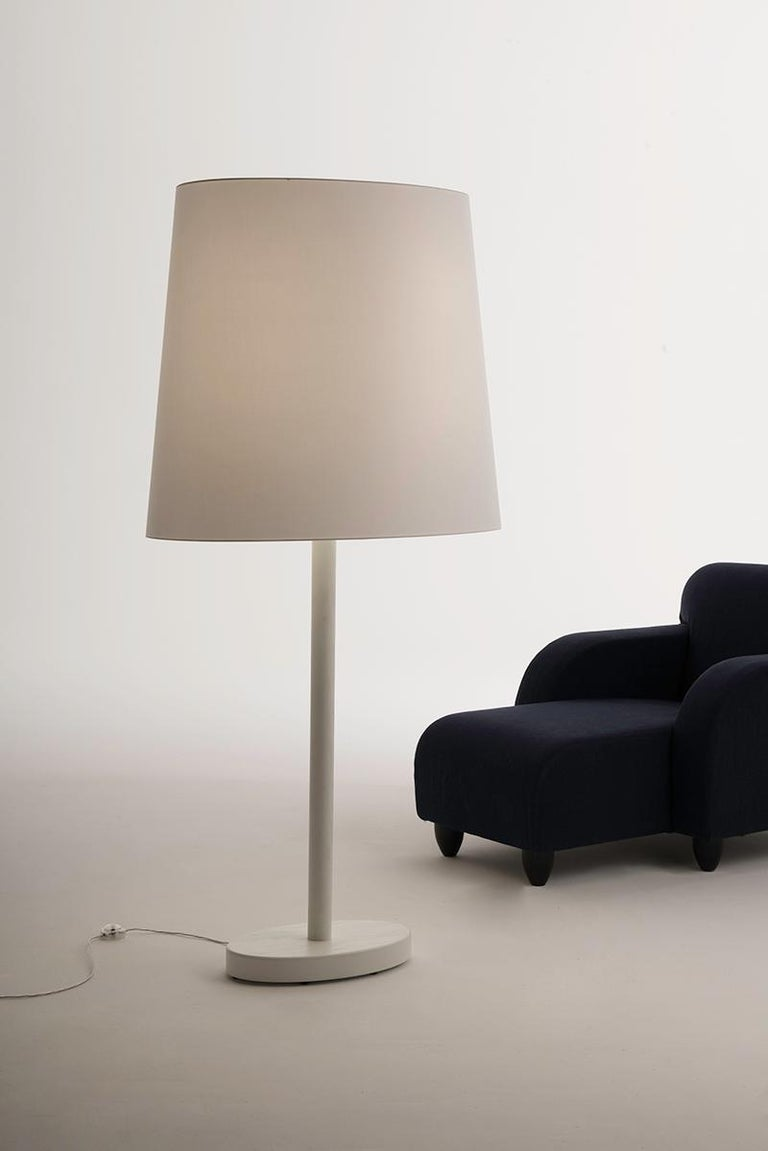 Designed by Aldo Cibic. Big one is an out-of-scale table lamp: a large floor lamp that provides a warm and diffused light. With its structure in white lacquered open-pore ashwood and the large white lampshade in chintz cotton, it fits in the room