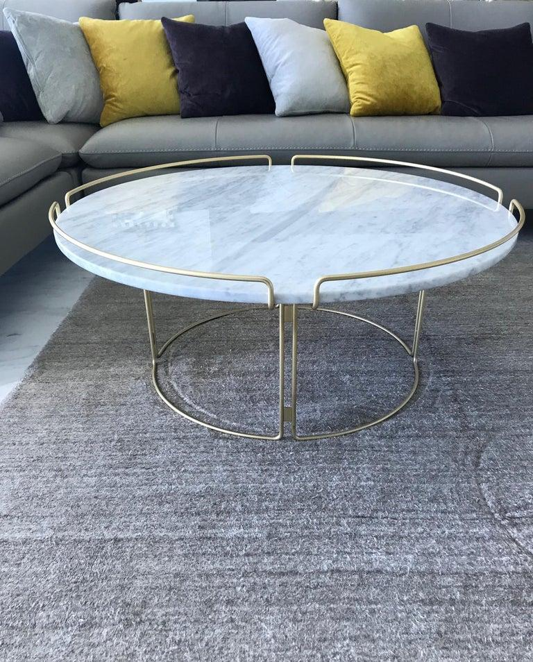 Stunning cocktail table designed by Fabrice Berrux for Roche Bobois. Table has a Mid-Century Modern inspired design. Features white Carrara marble top with round three-sided steel wire frame in lacquered matte gold or satin brass finish.