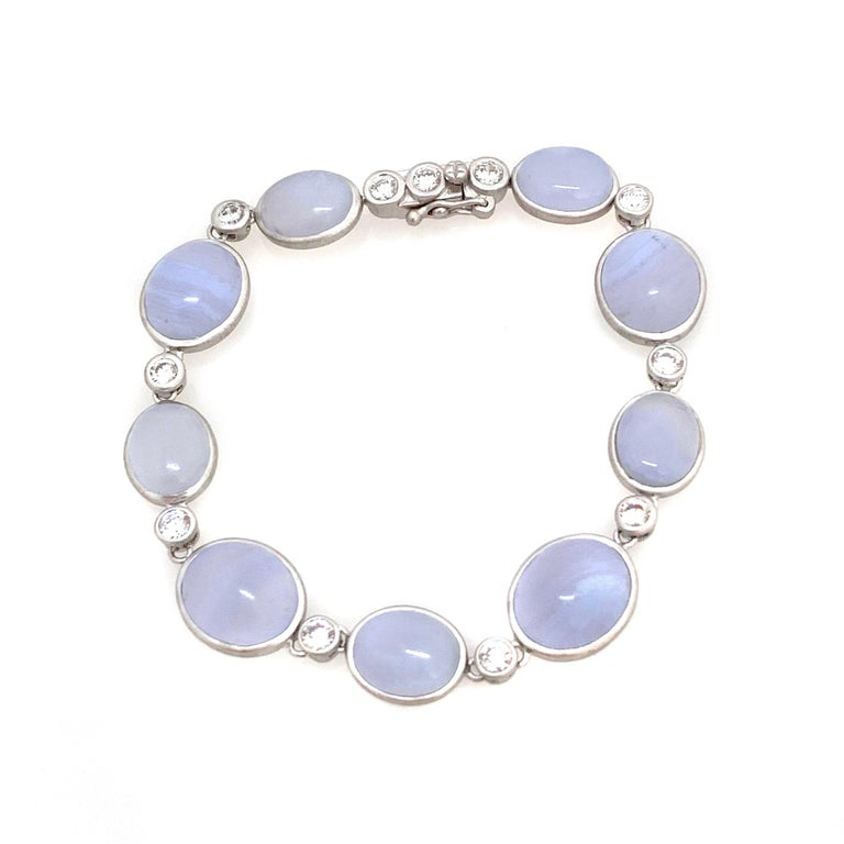 Discover Bijoux Num bezel-set oval chalcedony station bracelet.  This beautiful bracelet features 9 pieces of beautiful periwinkle purple-ish blue cabochon-cut oval chalcedony, handcrafted brushed satin texturing technique, and hand set in platinum