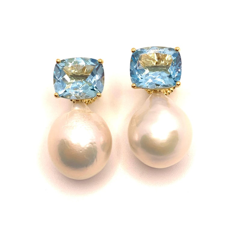 These stunning pair of earrings feature a pair of genuine cushion-cut sky blue topaz and lustrous white cultured baroque pearls, handset in 18K yellow gold vermeil over sterling silver. The pearls measure 16mm width and 20mm height offering