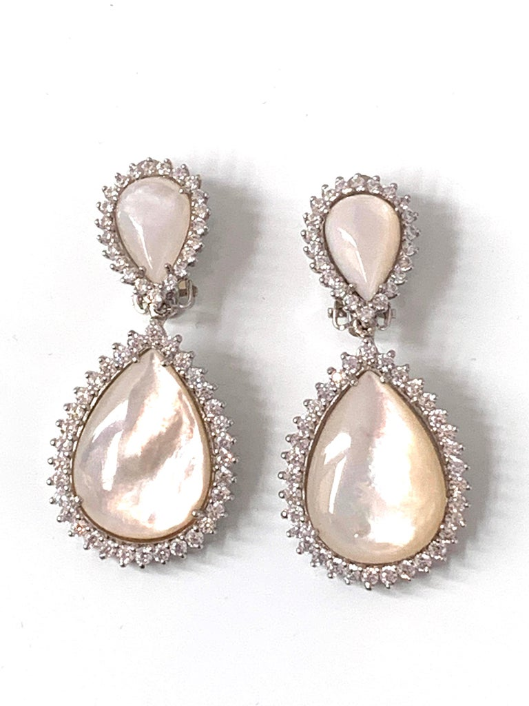 Double pear shape mother of pearl Drop Earrings surrounded with faux diamond CZ. These earrings feature 4 beautiful iridescent cabochon-cut pear shape mother of pearls and over 100pc of round cubic zirconia, handset in platinum rhodium plated