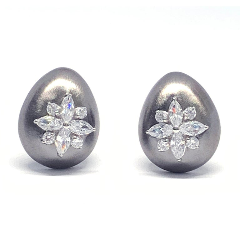 Stunning Egg-shape Clip-on Black Rhodium Earrings handset with Faux Diamond Cubic Zirconia. The earrings feature beautiful handmade brush satin texturing technique on gunmetal black rhodium plated sterling silver. Strong and comfortable clip back.