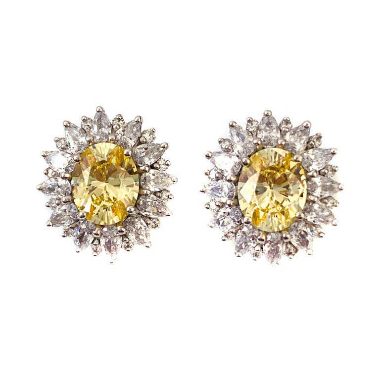 Bijoux Num fabulous faux canary diamond earrings. These earrings feature top quality oval-shape faux canary diamond, adorned with 48 pcs of pear shape and round cubic zirconia, handset in platinum rhodium plated sterling silver. The earrings measure
