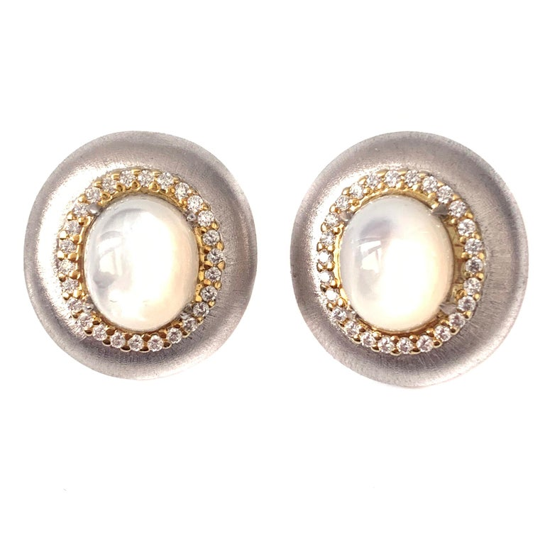 Bijoux Num Oval Mother of Pearl Oval Button Clip-on Earrings  The earrings features lustrous oval cabochon cut mother of pearl and round faux diamond cubic zirconia, handset in two-tone platinum rhodium & 18k gold plated sterling silver, and Italian
