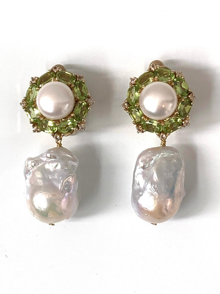 These earrings feature a large pair of high luster white baroque pearls (17mm). Both are elongated baroque shapes, blemish free and possess brilliant luster. Top part of the earrings feature a pair of high luster fresh water pearls, oval peridot,