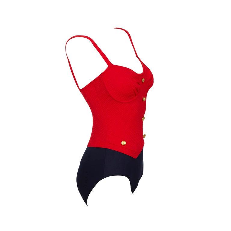 """Product details: Bill Blass - Red Seersucker Lycra Swimsuit - Gold Button Detail - x 2 Front Faux Pockets - Navy Plain Lycra Knicker Label: Bill Blass Era: c.1980 Fabric Content: Lycra Size: UK 10 Bust: 28"""" to 37"""" Min Waist: 24"""" to 32"""" Min Hips: 30"""""""