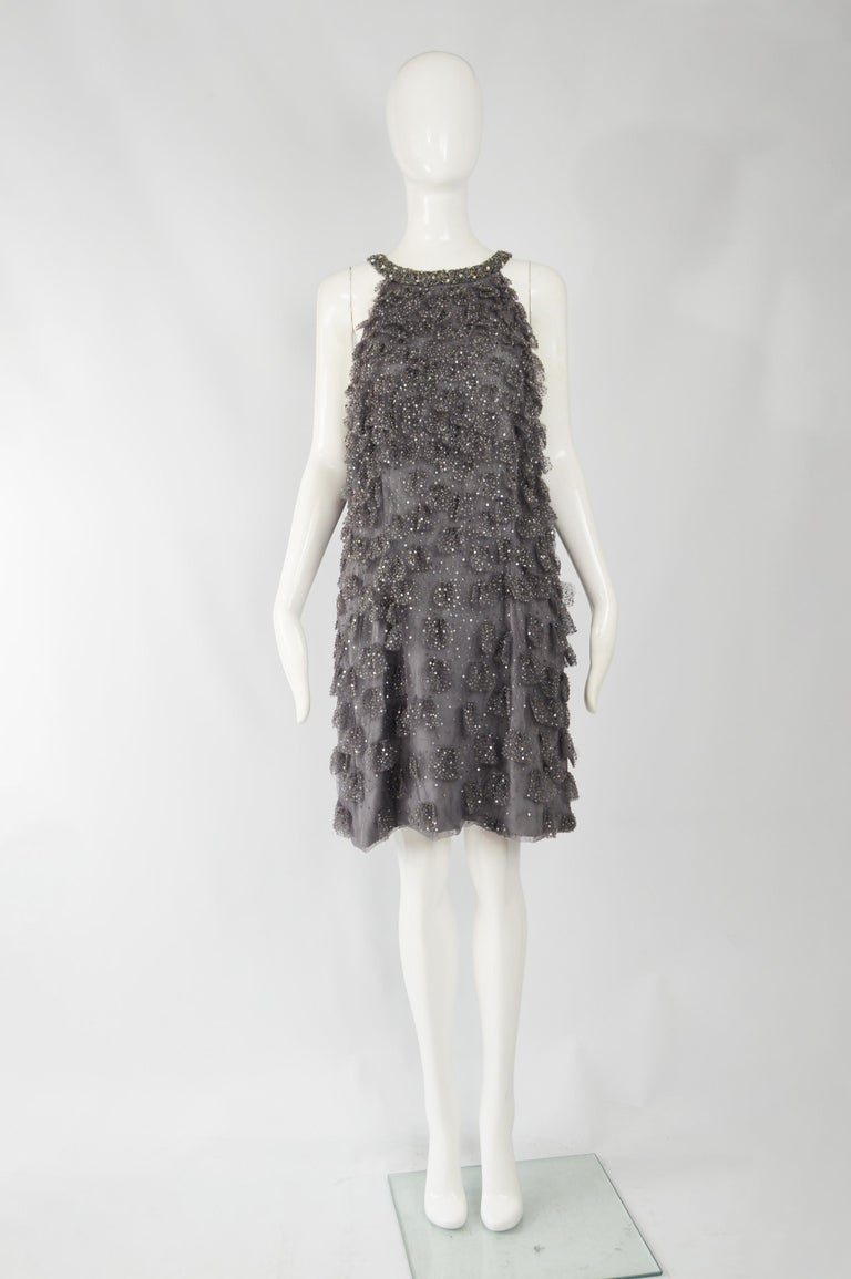 A stunning short, sleeveless evening dress by iconic American fashion designer, Bill Blass. In a grey ruffle and layered tulle with beads and sequins throughout giving a 60s inspired look perfect for a party.  Size: Unlabelled; fits roughly like a