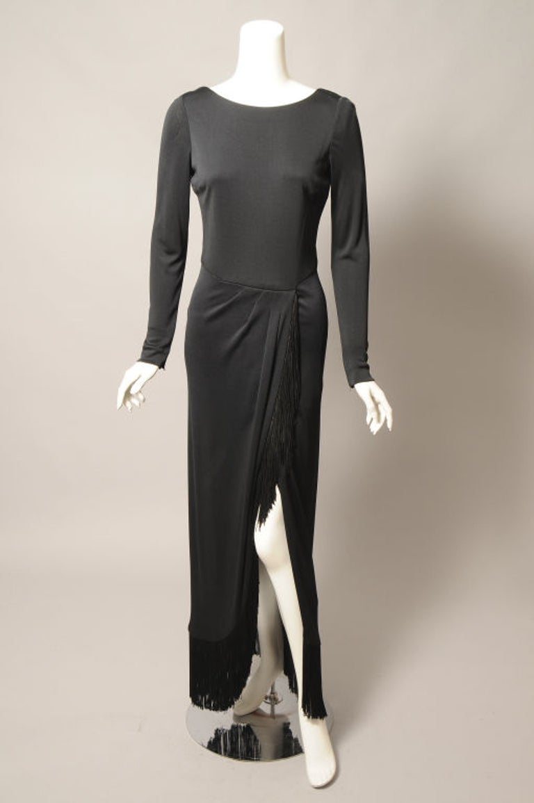 Sleek and elegant, this black silk crepe dress from Bill Blass is a little bit sexy too! The fringe trimmed skirt is slit right up to the waistline. The dress has a scoop neckline that is deeper in the back, long sleeves with zippers at the wrists