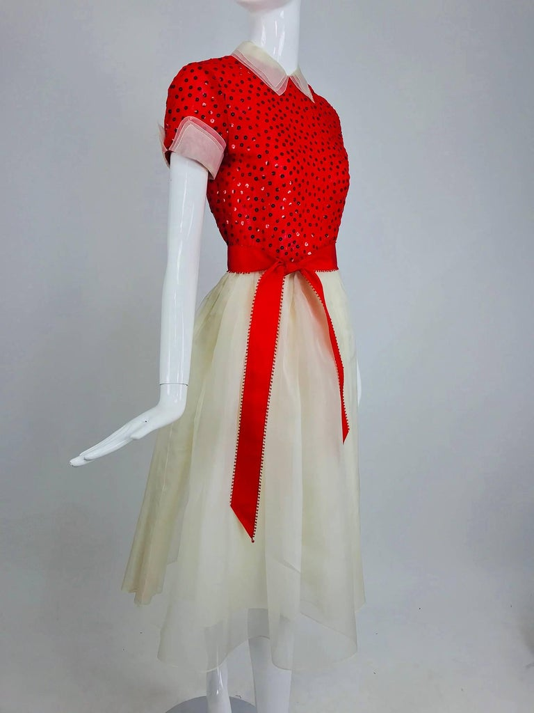 Bill Blass red and white sequined organza party, cocktail dress from the 1980s...Fitted bodice, short sleeve cocktail dress covered with red sequins and trimmed with white collar and cuffs...Seamed waist full skirt is white organza...Bodice is lined