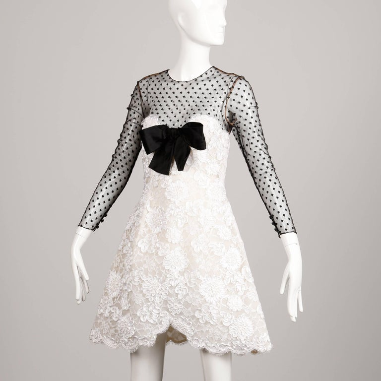 Darling black and white cocktail dress by Bill Blass. Sweetheart neckline and scalloped hem. Mesh sleeves and black silk bow detail at the bust. Fits like a modern size small. Bust: 34