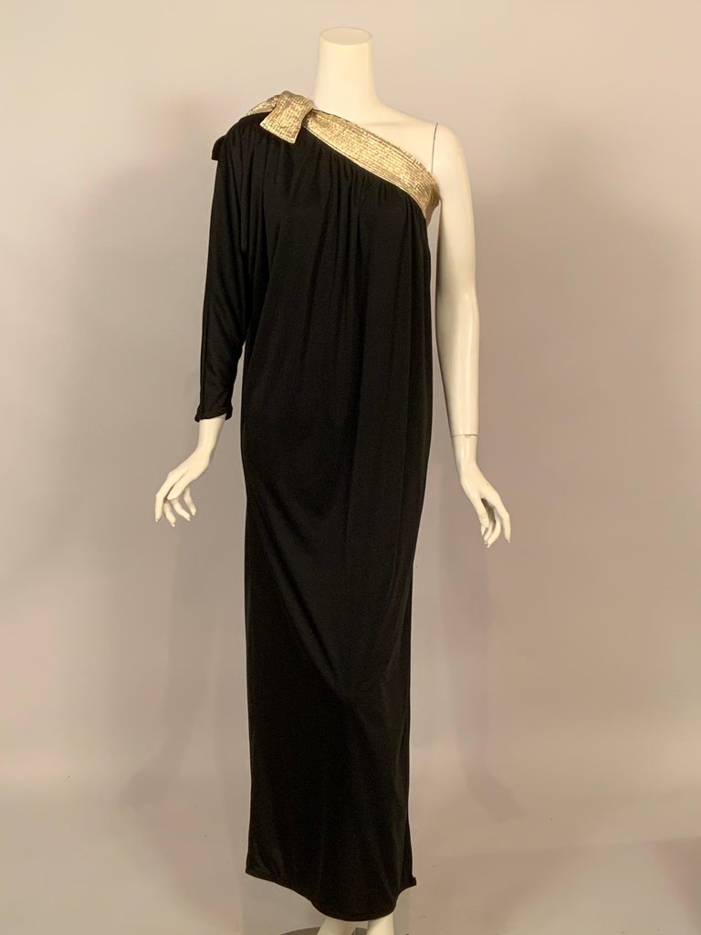 The elegance of an evening dress with the comfort of an at home outfit, Bill Tice designed both beautifully. This dress has a quilted band of metallic gold fabric at the bodice which ties above the single sleeve. The dress falls gently from this