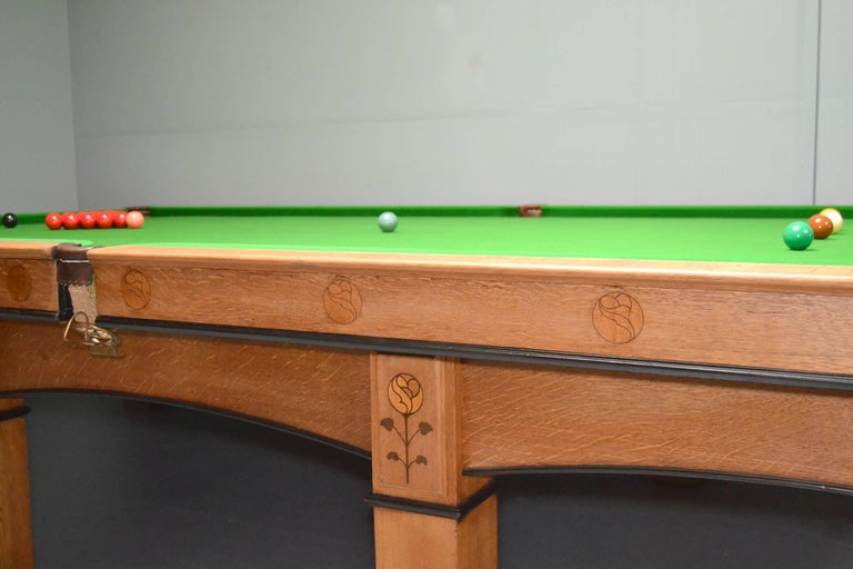 A solid oak full size Arts & Crafts Billiard, Snooker or Pool table, circa 1910 designed by G M Ellwood or George Walton and manufactured by Burroughes & Watts of London, see details below.   Standing on eight substantial oak legs with embellished