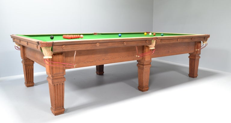 An attractive and very well made solid oak antique billiard or snooker table by Thurston of London circa 1910, standing on six tapering fluted or scalloped legs with applied rectangular cover panels, the cushions with applied decorative roundels.